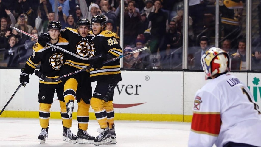 Boston Bruins right wing David Pastrnak (88) is congratulated by teammates Torey Krug (47) and Brad Marchand, left center, after his goal against Florida Panthers goalie Roberto Luongo (1) during the second period of an NHL hockey game in Boston, Monday, Dec. 5, 2016. (AP Photo/Charles Krupa)