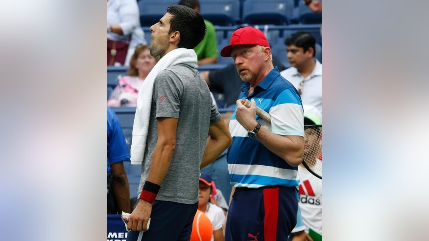 "FILE - In this Sept. 2, 2016, file photo, Novak Djokovic, of Serbia, left, talks with his coach Boris Becker during a practice session after his opponent Mikhail Youzhny, of Russia, retired in the first set of their match in the third round of the U.S. Open tennis tournament, in New York. Djokovic says he and coach Boris Becker are splitting up after three seasons together. Djokovic posted a statement on Facebook on Tuesday, Dec. 6, 2016, saying the duo ""jointly decided to end our cooperation.""(AP Photo/Jason DeCrow, File)"