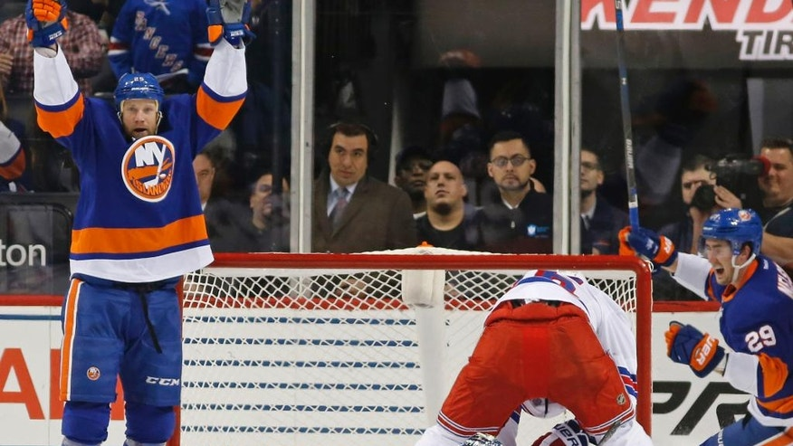 New York Islanders' left wing Jason Chimera (25) and Islanders' left wing Brock Nelson (29) celebrate after Chimera scored a goal on New York Rangers Henrik Lundqvist (30) of Sweden during the first period of an NHL hockey game, Tuesday, Dec. 6, 2016, in New York. (AP Photo/Kathy Willens)
