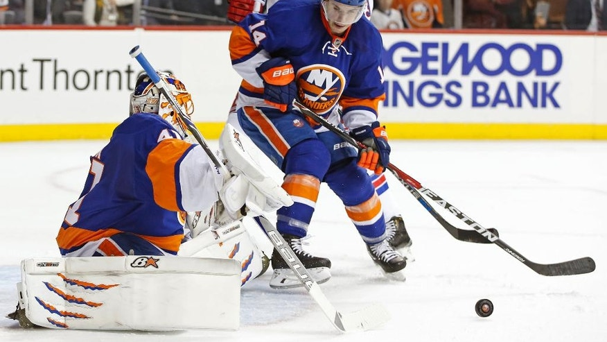 New York Islanders' goalie Jaroslav Halak (41), of Slovakia, deflects a shot with Islanders' defenseman Thomas Hickey (14) fending off New York Rangers' center Kevin Hayes (13) during the first period of an NHL hockey game, Tuesday, Dec. 6, 2016, in New York. (AP Photo/Kathy Willens)