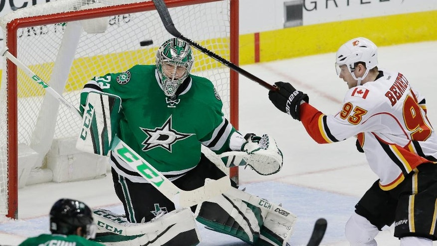 Calgary Flames center Sam Bennett (93) tries to get his stick on the puck as Dallas Stars goalie Antti Niemi (31) defends the goal during the second period of an NHL hockey game in Dallas, Tuesday, Dec. 6, 2016. (AP Photo/LM Otero)