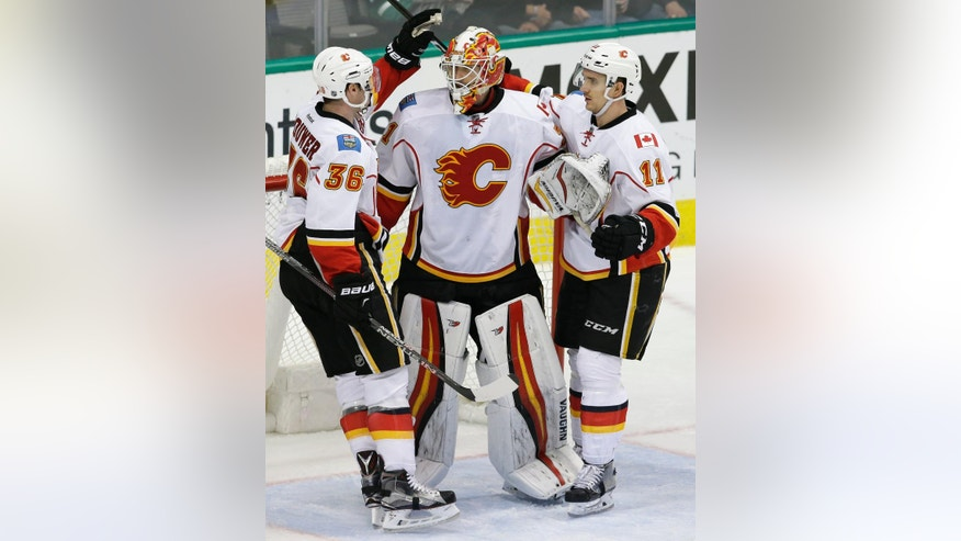 Calgary Flames goalie Chad Johnson (31) celebrates the win with teammates Troy Brouwer (36) and Mikael Backlund (11) after the third period of an NHL hockey game against the Dallas Stars in Dallas, Tuesday, Dec. 6, 2016. The Flames won 2-1. (AP Photo/LM Otero)
