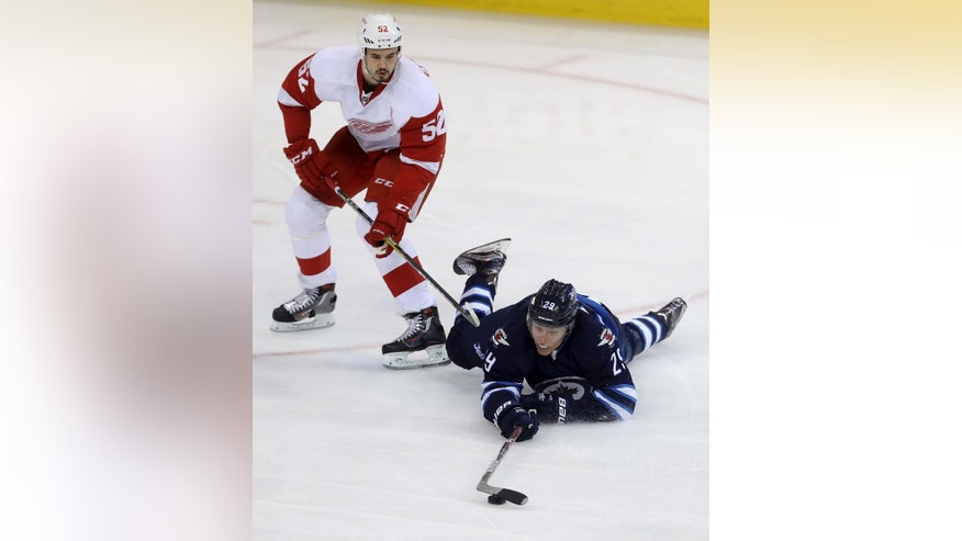 Detroit Red Wings' Jonathan Ericsson (52) trips up Winnipeg Jets' Patrik Laine (29) during first period NHL hockey action in Winnipeg, Tuesday, Dec. 6, 2016. (Trevor Hagan/The Canadian Press via AP)