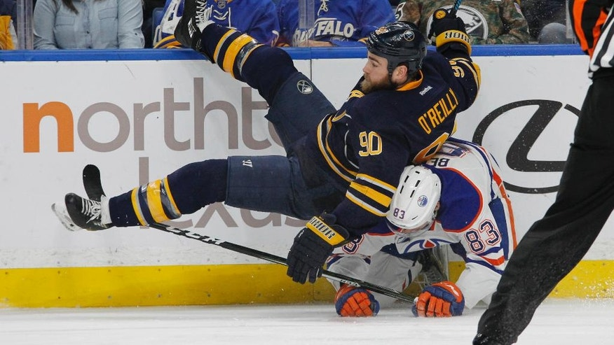 Buffalo Sabres Ryan O'Reilly (90) is upended by Edmonton Oilers Matthew Benning (83) during the first period of an NHL hockey game, Tuesday, Dec. 6, 2016, in Buffalo, N.Y. (AP Photo/Jeffrey T. Barnes)