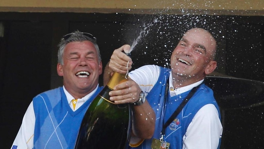 FILE - In this Monday, Oct. 4, 2010 file photo, Europe's assistant captains Thomas Bjorn, right, and Darren Clarke celebrate with champagne after winning the 2010 Ryder Cup golf tournament at the Celtic Manor Resort in Newport, Wales. Bjorn is the first Scandinavian to be appointed captain of Europe's Ryder Cup team. The 45-year-old Dane will lead the team against the United States in 2018 at Le Golf National in Paris after being chosen by a five-man panel, including Europe's past three captains. (AP Photo/Jon Super, File)