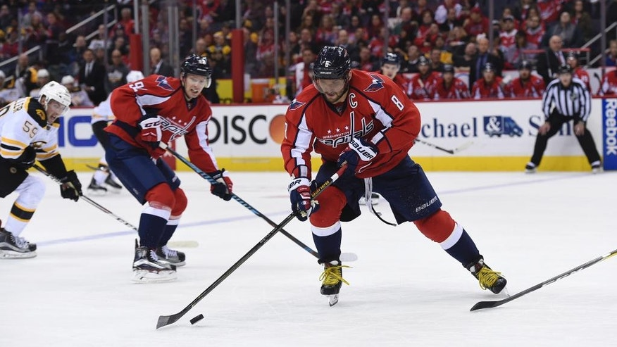 Washington Capitals left wing Alex Ovechkin (8), of Russia, handles the puck past Boston Bruins center Tim Schaller (59) and Washington Capitals center Evgeny Kuznetsov (92), of Russia, during second period of an NHL hockey game, Wednesday, Dec. 7, 2016, in Washington. (AP Photo/Molly Riley)
