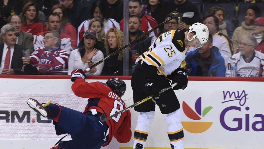 Washington Capitals left wing Alex Ovechkin (8), of Russia, hits the wall in front of Boston Bruins defenseman Brandon Carlo (25) during second period of an NHL hockey game, Wednesday, Dec. 7, 2016, in Washington. (AP Photo/Molly Riley)