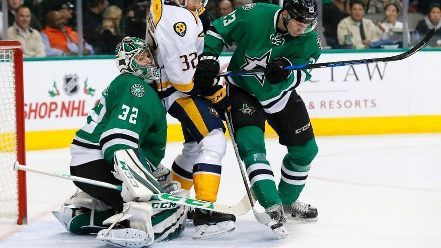 Dallas Stars' Kari Lehtonen (32), of Finland, fights off pressure from Nashville Predators' Frederick Gaudreau (32) as the Stars' Esa Lindell (23), of Finlan,d clears the puck with his skate in the second period of an NHL hockey game, Thursday, Dec. 8, 2016, in Dallas. (AP Photo/Tony Gutierrez)