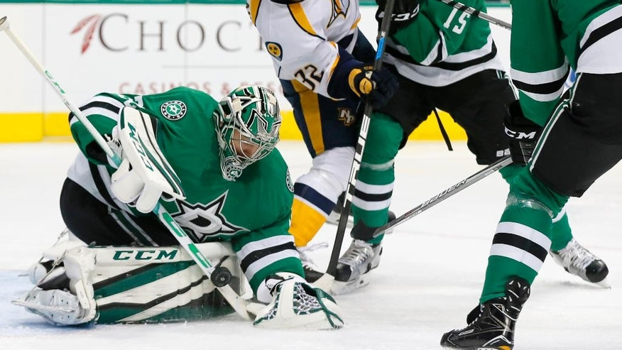 Dallas Stars goalie Kari Lehtonen (32) of Finland makes a save as defenseman Patrik Nemeth (15) of Sweden helps against pressure from Nashville Predators' Frederick Gaudreau (32) in the second period of an NHL hockey game, Thursday, Dec. 8, 2016, in Dallas. (AP Photo/Tony Gutierrez)