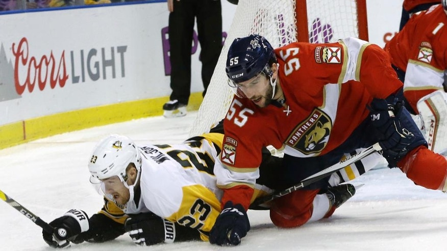 Pittsburgh Penguins left wing Scott Wilson (23) and Florida Panthers defenseman Jason Demers (55) go for the puck during the first period of an NHL hockey game, Thursday, Dec. 8, 2016, in Sunrise, Fla. (AP Photo/Lynne Sladky)
