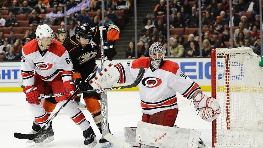 Carolina Hurricanes' Ron Hainsey, left, and Anaheim Ducks' Ryan Kesler watch as the puck passes by Hurricanes goalie Cam Ward during the second period of an NHL hockey game Wednesday, Dec. 7, 2016, in Anaheim, Calif. (AP Photo/Jae C. Hong)