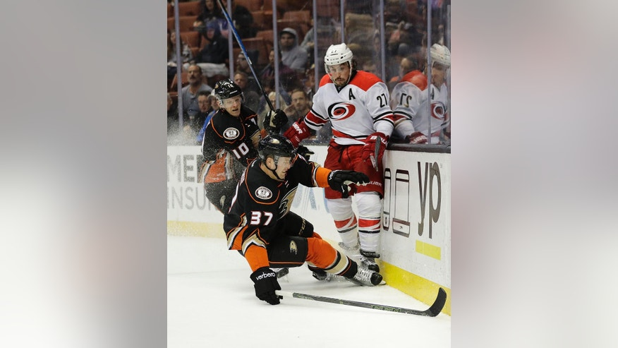 Anaheim Ducks' Nick Ritchie skids in front of Ducks' Corey Perry, background left, and Carolina Hurricanes' Justin Faulk during the second period of an NHL hockey game Wednesday, Dec. 7, 2016, in Anaheim, Calif. (AP Photo/Jae C. Hong)