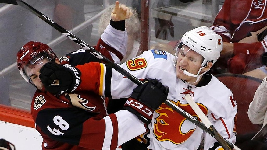 Calgary Flames left wing Matthew Tkachuk (19) mixes it up with Arizona Coyotes left wing Jordan Martinook (48) during the second period of an NHL hockey game Thursday, Dec. 8, 2016, in Glendale, Ariz. (AP Photo/Ross D. Franklin)