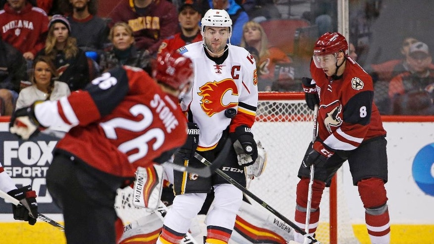 Calgary Flames defenseman Mark Giordano (5) takes a slapshot off his stomach from Arizona Coyotes defenseman Michael Stone (26) as Coyotes' right wing Tobias Rieder (8) looks for a possible rebound during the first period of an NHL hockey game Thursday, Dec. 8, 2016, in Glendale, Ariz. (AP Photo/Ross D. Franklin)