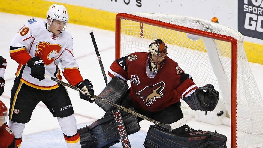 Arizona Coyotes goalie Mike Smith, right, makes a save on a redirect from Calgary Flames left wing Matthew Tkachuk (19) during the second period of an NHL hockey game Thursday, Dec. 8, 2016, in Glendale, Ariz. (AP Photo/Ross D. Franklin)