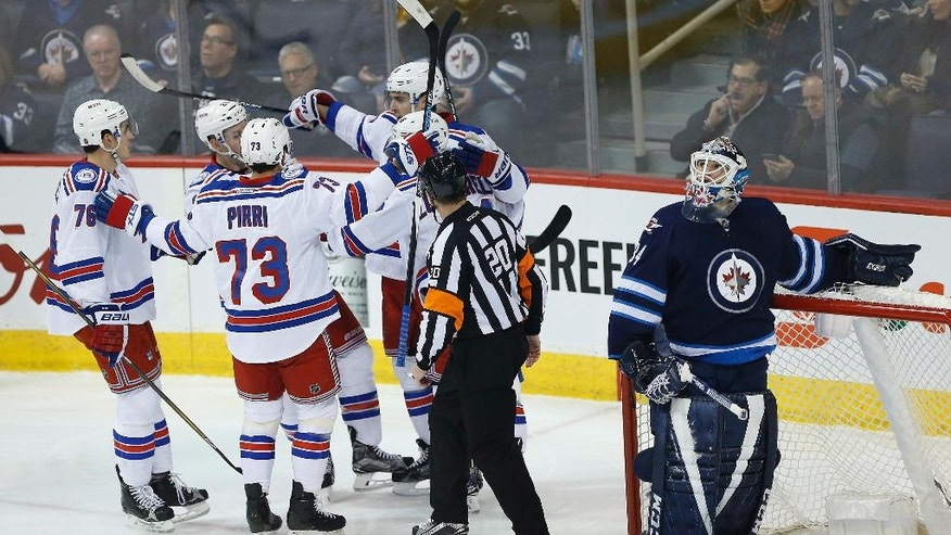 Winnipeg Jets goaltender Michael Hutchinson (34) looks up at the replay as New York Rangers' Brady Skjei (76), Brandon Pirri (73), Derek Stepan (21), Mats Zuccarello (36) and Chris Kreider (20) celebrate Kreider's goal during the first period of an NHL hockey game, Thursday, Dec. 8, 2016 in Winnipeg, Manitoba.  (John Woods/The Canadian Press via AP)