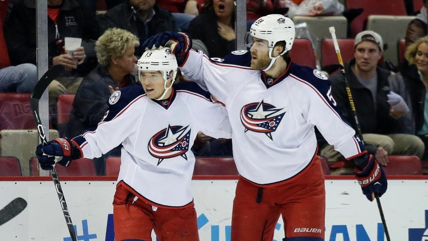 Columbus Blue Jackets right wing Cam Atkinson, left, is congratulated by defenseman David Savard after scoring against the Detroit Red Wings during the first period of an NHL hockey game Friday, Dec. 9, 2016, in Detroit. (AP Photo/Duane Burleson)