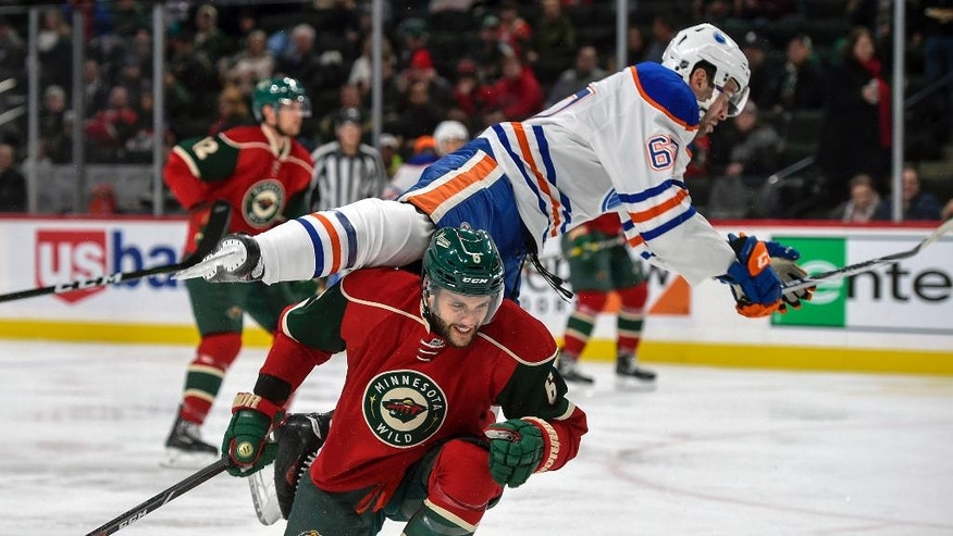 Edmonton Oilers' Benoit Pouliot flies over the top of Minnesota Wild's defenseman Marco Scandella, bottom, during the second period of an NHL hockey game, Friday, Dec. 9, 2016, in St. Paul, Minn. (AP Photo/Craig Lassig)