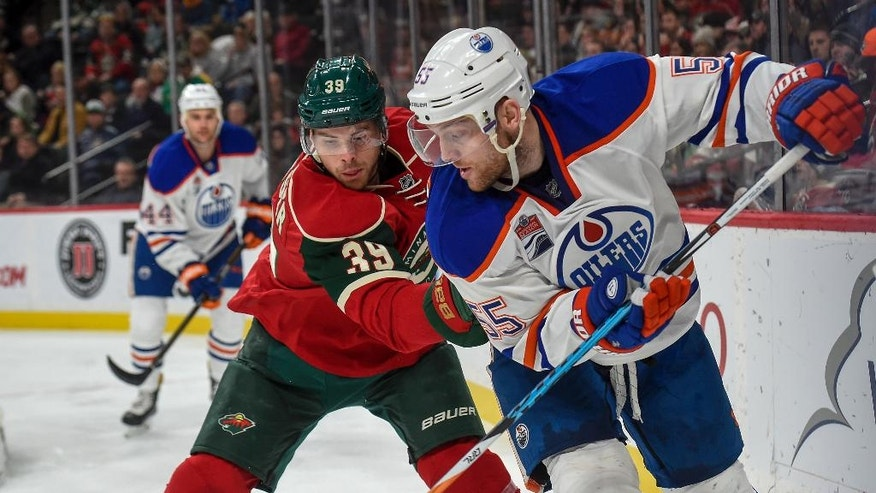 Edmonton Oilers' center Mark Letestu, right, passes the puck back and through the legs of Minnesota Wild defenseman Nate Prosser (39) during the second period of an NHL hockey game, Friday, Dec. 9, 2016, in St. Paul, Minn. (AP Photo/Craig Lassig)