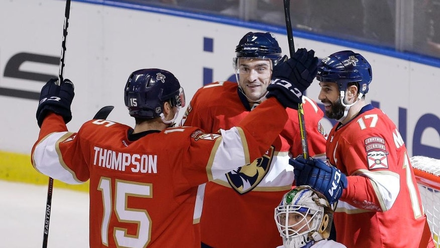 Florida Panthers center Derek MacKenzie (17) celebrates with teammates Florida Panthers right wing Paul Thompson (15) and Florida Panthers center Colton Sceviour (7) after MacKenzie scored against Vancouver Canucks goalie Jacob Markstrom (25) in the second period of an NHL hockey game, Saturday, Dec. 10, 2016, in Sunrise, Fla. (AP Photo/Alan Diaz)
