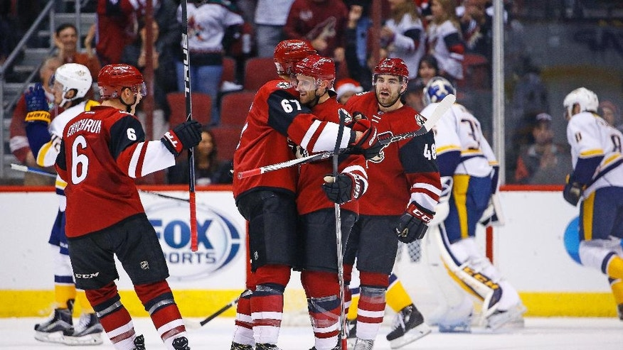 Arizona Coyotes defenseman Alex Goligoski, center, celebrates his goal against the Nashville Predators with left wing Lawson Crouse (67), left wing Jordan Martinook (48) and defenseman Jakob Chychrun (6) during the first period of an NHL hockey game Saturday, Dec. 10, 2016, in Glendale, Ariz. (AP Photo/Ross D. Franklin)