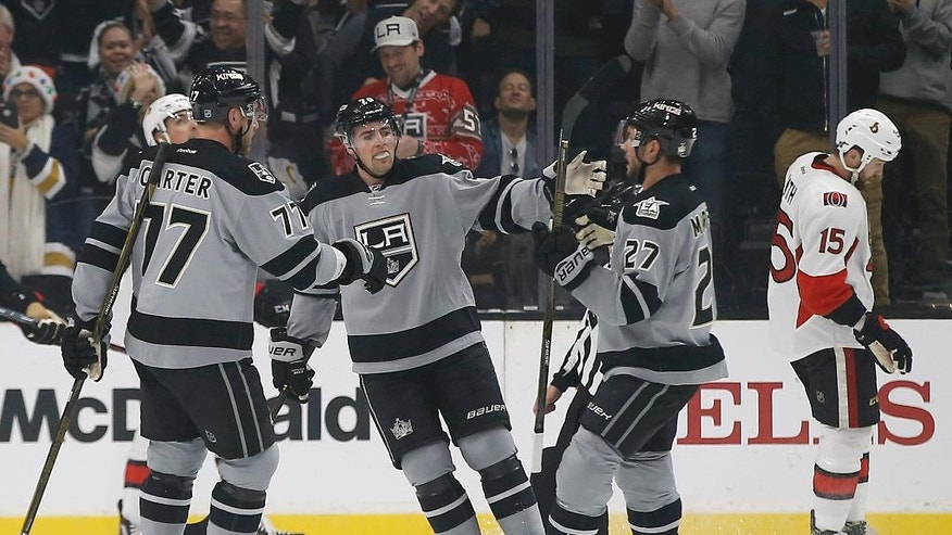 Ottawa Senators center Zack Smith (15) skates away as Los Angeles Kings center Jeff Carter (77) and left wing Tanner Pearson, center, congratulate defenseman Alec Martinez (27) for scoring a goal during the first period of an NHL hockey game in Los Angeles, Saturday, Dec. 10, 2016. (AP Photo/Alex Gallardo)