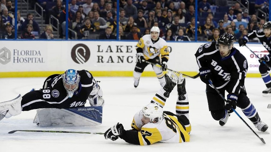 Pittsburgh Penguins center Sidney Crosby (87) scores past Tampa Bay Lightning goalie Andrei Vasilevskiy (88), of Russia, while sliding across the ice during the first period of an NHL hockey game Saturday, Dec. 10, 2016, in Tampa, Fla. (AP Photo/Chris O'Meara)