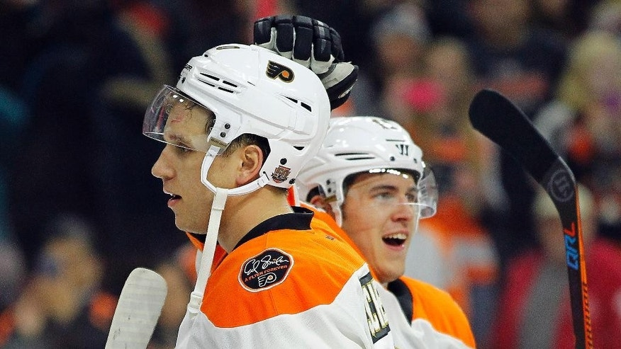 Philadelphia Flyers' Brayden Schenn, who scored three goals for a hat trick, gets a tap on the head from Travis Konecny as the team celebrates their 4-2 win over the Dallas Stars, Saturday, Dec. 10, 2016, in Philadelphia. The Flyers won 4-2. (AP Photo/Tom Mihalek)