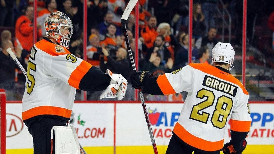 Philadelphia Flyers' Steve Mason, left, and Claude Giroux tap gloves with seconds left in the third period as the team begins to celebrates their 4-2 win over the Dallas Stars in an NHL hockey game, Saturday, Dec. 10, 2016, in Philadelphia. (AP Photo/Tom Mihalek)