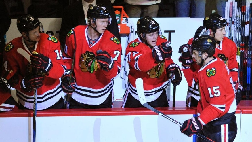 Chicago Blackhawks' Artem Anisimov (15) of Russia, celebrates with teammates on the bench after scoring a goal during the second period of an NHL hockey game against the Dallas Stars on Sunday, Dec. 11, 2016, in Chicago. (AP Photo/Paul Beaty)