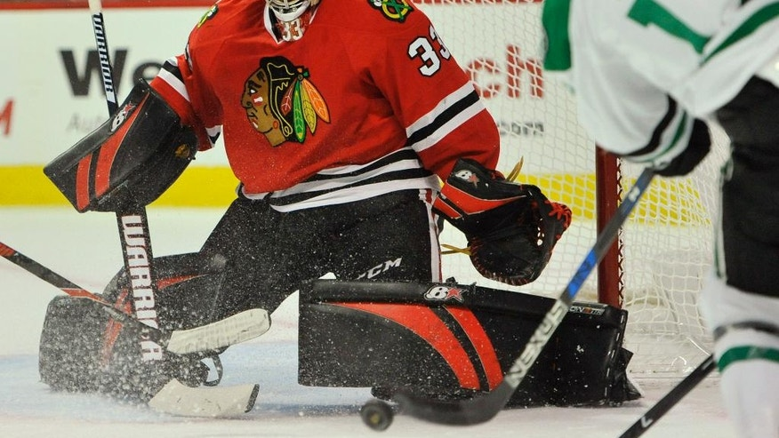 Chicago Blackhawks goalie Scott Darling (33) makes a save against Dallas Stars' Devin Shore (17) during the first period of an NHL hockey game Sunday, Dec. 11, 2016, in Chicago. (AP Photo/Paul Beaty)