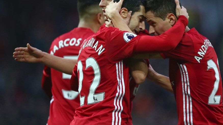 Manchester United's Henrikh Mkhitaryan celebrates scoring their first goal with teammate Ander Herrera, right, during the Premier League soccer match between Manchester United and Tottenham Hotspur at Old Trafford in Manchester, England, Sunday, Dec. 11, 2016. (AP Photo/Dave Thompson)