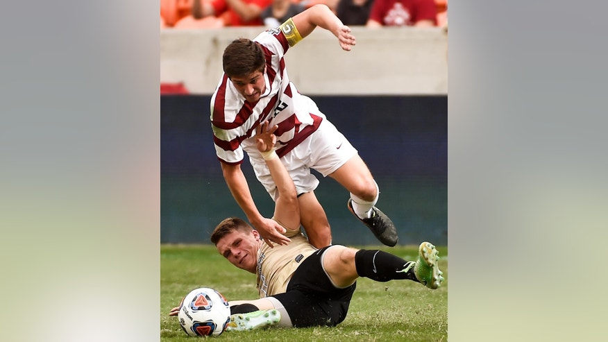 Wake Forest midfielder Brad Dunwell, bottom, tackles Stanford midfielder Drew Skundrich during the first half of an NCAA college soccer game, Sunday, Dec. 11, 2016, in Houston. (AP Photo/Eric Christian Smith)