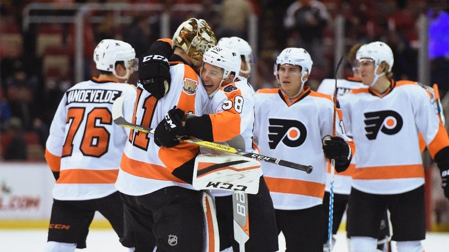 Philadelphia Flyers goalie Anthony Stolarz (41) is congratulated by left wing Taylor Leier (58) after defeating the Red Wings 1-0 in overtime of an NHL hockey game in Detroit, Sunday, Dec. 11, 2016. (AP Photo/Jose Juarez)