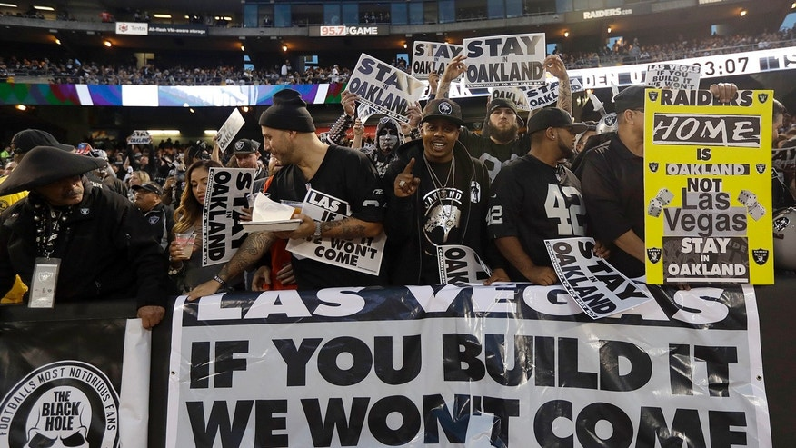 FILE - In this Nov. 6, 2016, file photo, Oakland Raiders fans hold up signs about the team's possible move to Las Vegas during an NFL football game between the Raiders and the Denver Broncos in Oakland, Calif.