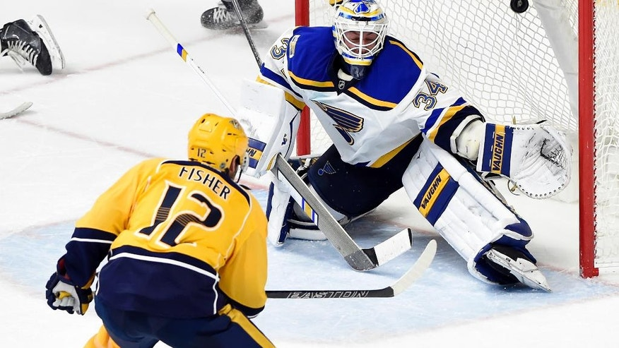 Nashville Predators center Mike Fisher (12) scores the go-ahead goal against St. Louis Blues goalie Jake Allen (34) during the third period of an NHL hockey game Tuesday, Dec. 13, 2016, in Nashville, Tenn. The Predators won 6-3. (AP Photo/Mark Zaleski)
