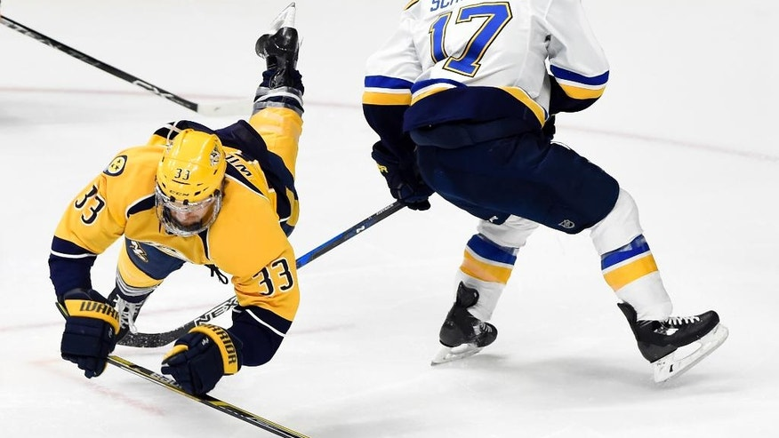 Nashville Predators left wing Colin Wilson (33) falls over the stick of St. Louis Blues left wing Jaden Schwartz (17) going for the puck during the third period of an NHL hockey game, Tuesday, Dec. 13, 2016, in Nashville, Tenn. The Predators won 6-3. (AP Photo/Mark Zaleski)