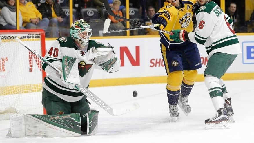 Nashville Predators right wing James Neal (18) reaches for the puck between Minnesota Wild goalie Devan Dubnyk (40) and defenseman Marco Scandella (6) during the second period of an NHL hockey game Thursday, Dec. 15, 2016, in Nashville, Tenn. (AP Photo/Mark Humphrey)