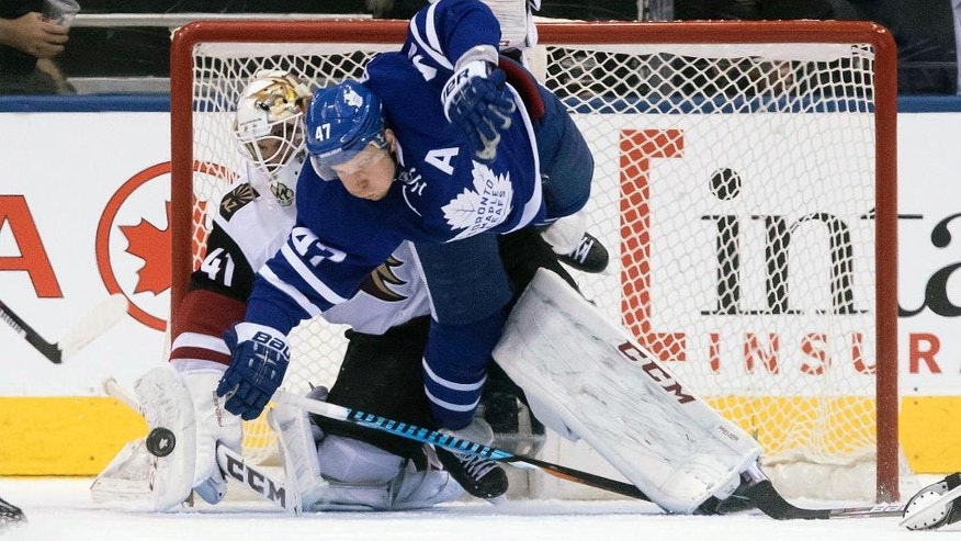 Arizona Coyotes goalie Mike Smith makes a save in front of Toronto Maple Leafs center Leo Komarov  during the third period of an NHL hockey game, Thursday, Dec. 15, 2016 in Toronto. (Chris Young/The Canadian Press via AP)
