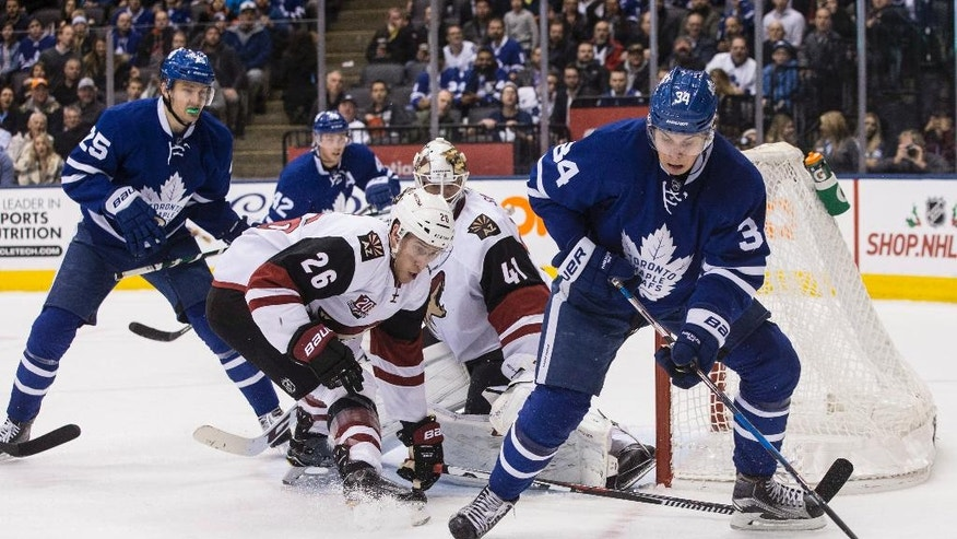 Toronto Maple Leafs center Auston Matthews, right, tries to play the puck as Arizona Coyotes defenseman Michael Stone (26) and goalie Mike Smith defend during second-period NHL hockey game action in Toronto, Thursday, Dec. 15, 2016. (Chris Young/The Canadian Press via AP)