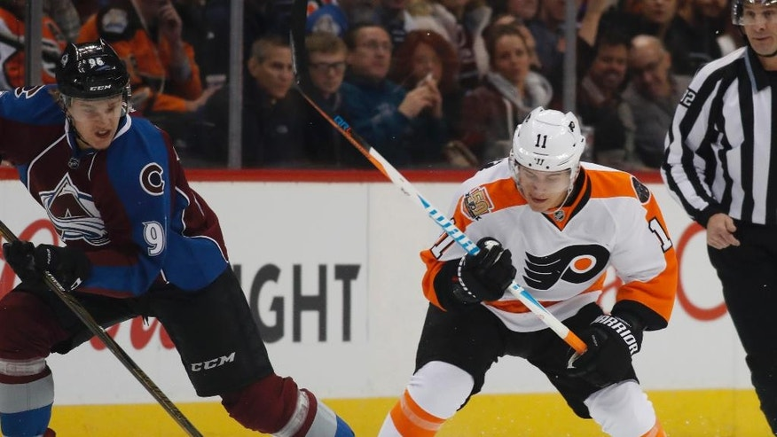 Philadelphia Flyers center Travis Konecny, right, fights for control of the puck with Colorado Avalanche right wing Mikko Rantanen, of Finland, in the first period of an NHL hockey game Wednesday, Dec. 14, 2016, in Denver. (AP Photo/David Zalubowski)