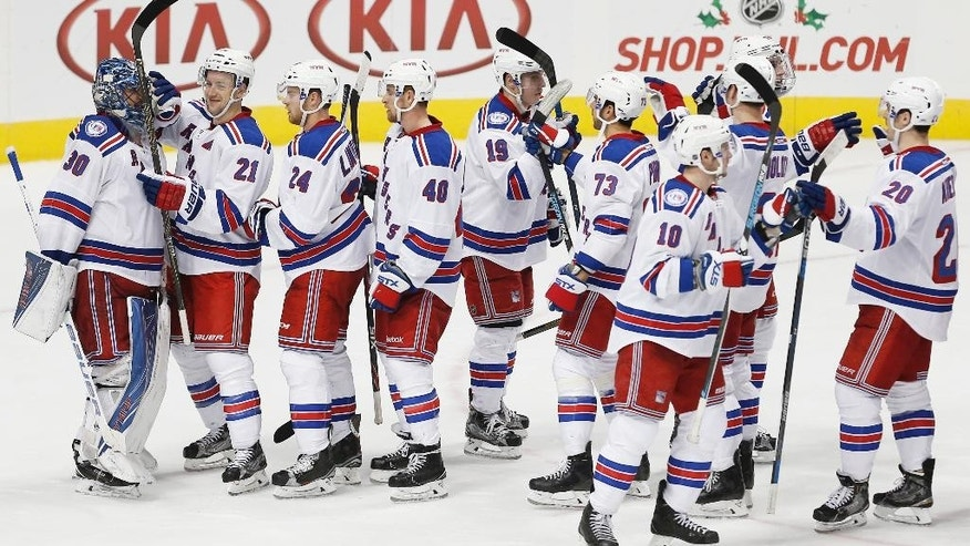 The New York Rangers celebrates a 2-0 win over the Dallas Stars after an NHL hockey game, Thursday, Dec. 15, 2016, in Dallas. (AP Photo/Brandon Wade)