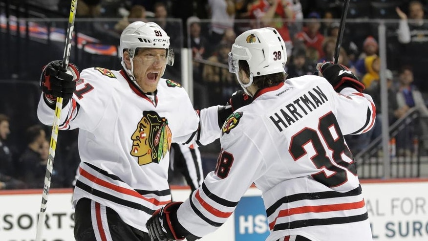 Chicago Blackhawks right wing Marian Hossa, left, celebrates with Ryan Hartman (38) after scoring a goal during the first period of an NHL hockey game against the New York Islanders Thursday, Dec. 15, 2016, in New York. (AP Photo/Frank Franklin II)