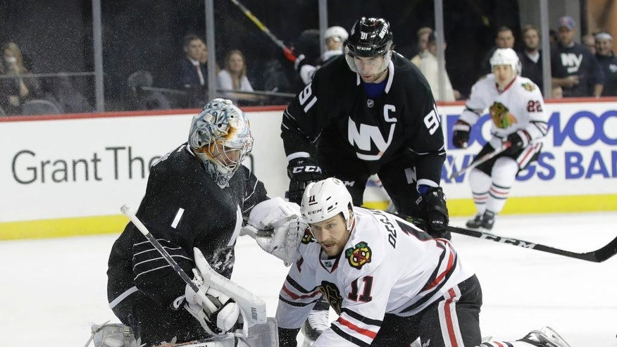 New York Islanders goalie Thomas Greiss stops a shot on the goal by Chicago Blackhawks' Andrew Desjardins (11) during the first period of an NHL hockey game Thursday, Dec. 15, 2016, in New York. (AP Photo/Frank Franklin II)