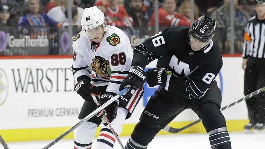 Chicago Blackhawks' Patrick Kane (88) and New York Islanders' Nikolay Kulemin (86) fight for the puck during the first period of an NHL hockey game Thursday, Dec. 15, 2016, in New York. (AP Photo/Frank Franklin II)
