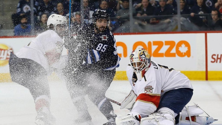 Florida Panthers goaltender Roberto Luongo (1) saves a shot from Winnipeg Jets' Mathieu Perreault (85) as Aaron Ekblad (5) defends during second-period NHL hockey game action in Winnipeg, Manitoba, on Thursday, Dec. 15, 2016. (John Woods/The Canadian Press via AP)