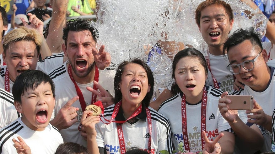 FILE - In this May 7, 2016 file photo, Eastern Sports Club head coach Chan Yuen-ting, center, celebrates with her players after winning the Hong Kong Premier League title in Hong Kong. World Cup winning coach Luiz Felipe Scolari's first task in trying to take Guangzhou Evergrande to a third Asian Champions League will be to face a team coached by the 28 year-old woman. The draw has pitted the Chinese powerhouse against Hong Kong club Eastern F.C., whose coach Chan became the first woman to lead a men's team to a title in a professional top flight league when Eastern won the 2016 Hong Kong Premier League. (AP Photo/Kin Cheung, File)