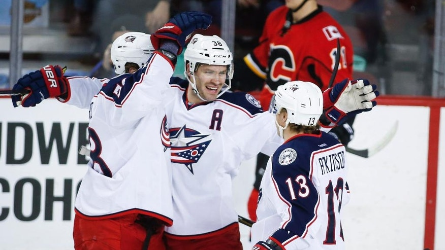 Columbus Blue Jackets' Boone Jenner, center, celebrates his goal with teammates David Savard, left, and Cam Atkinson during the first period of an NHL hockey game against the Calgary Flames, Friday, Dec. 16, 2016 in Calgary, Alberta. (Jeff McIntosh/The Canadian Press via AP)
