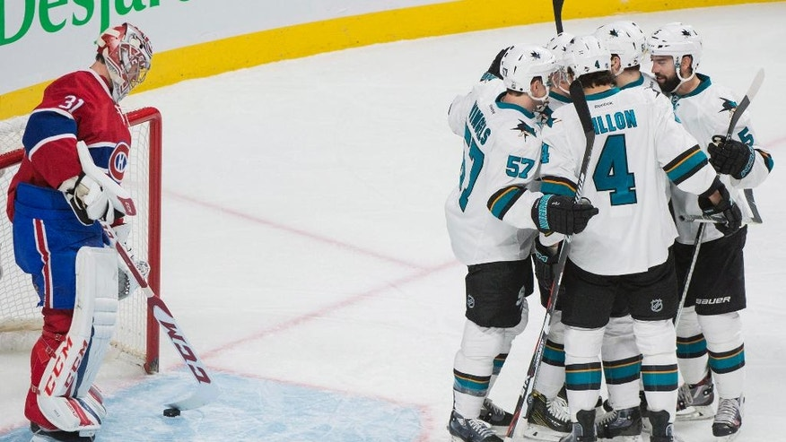 Montreal Canadiens goaltender Carey Price looks down at the puck as San Jose Sharks players celebrate a goal by teammate Melker Karlsson during the second period of an NHL hockey game, Friday, Dec. 16, 2016 in Montreal. (Graham Hughes/The Canadian Press via AP)