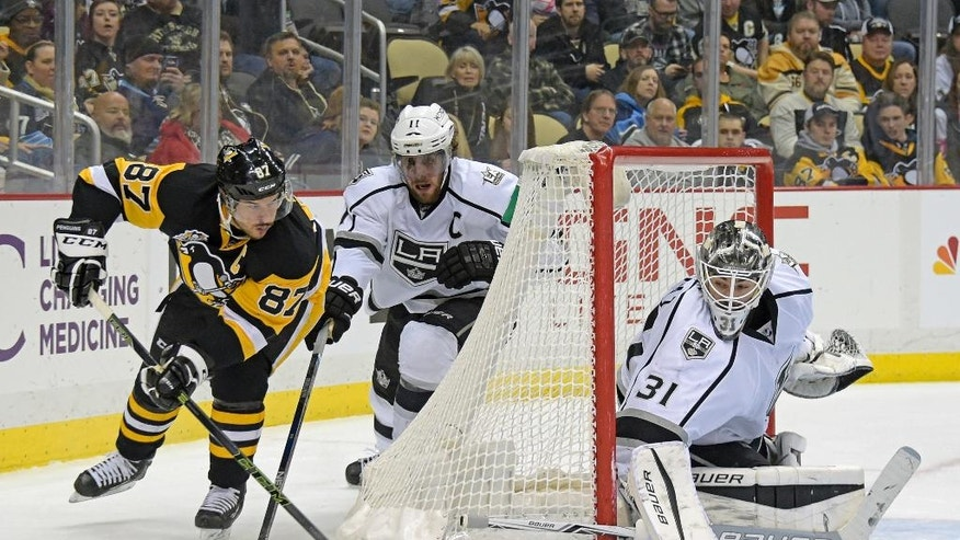 Pittsburgh Penguins center Sidney Crosby (87) passes the puck past Los Angeles Kings center Anze Kopitar (11) and Los Angeles Kings goalie Peter Budaj (31) during the second period of an NHL hockey game on Friday, Dec. 16, 2016, in Pittsburgh. (AP Photo/Fred Vuich)
